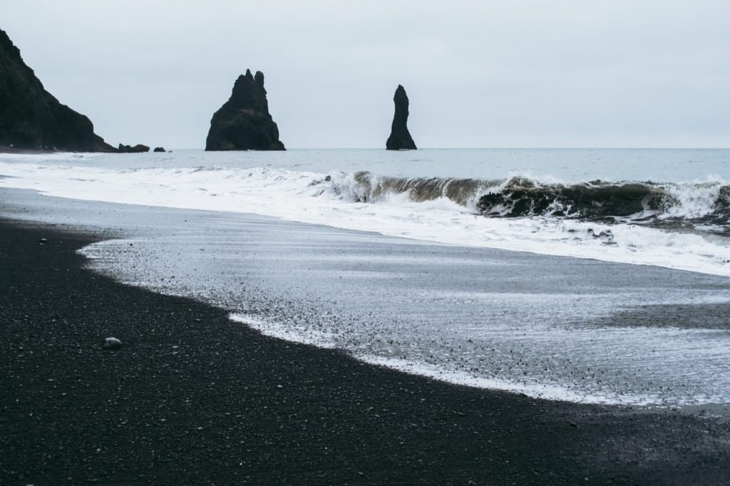 Black sand beach in Iceland with waves from the Atlantic ocean covering the sand