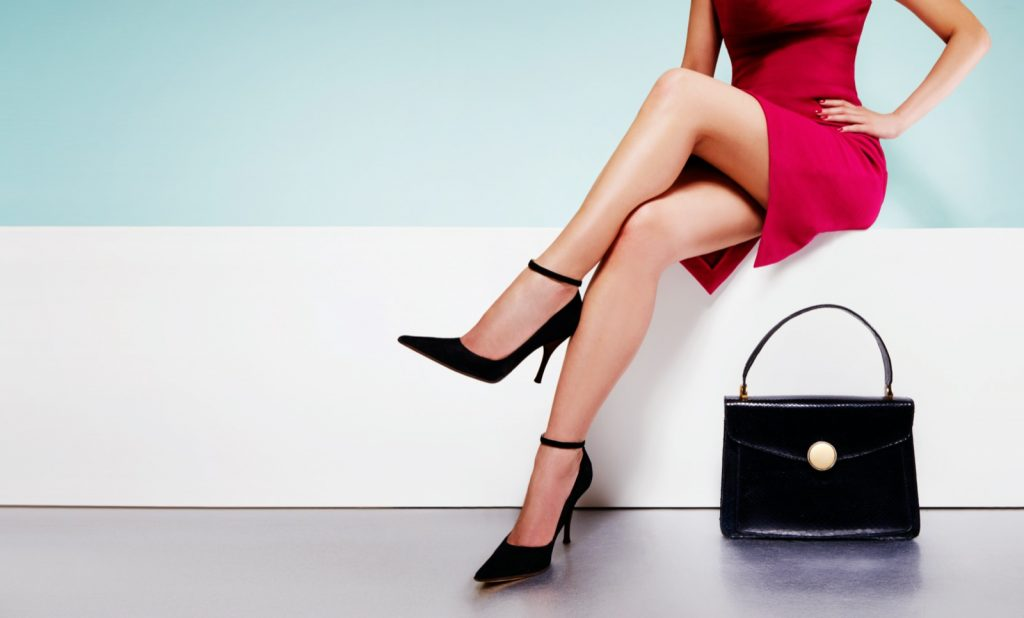 Woman in red dress and black shoes sitting with purse in front of her