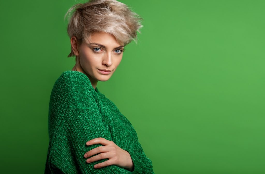 Fashion portrait of woman with blond short hair wearing green sweater
