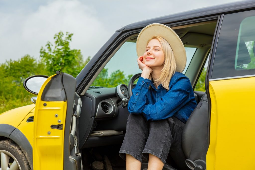 Blonde girl with hat sitting in a yellow car at the countryside