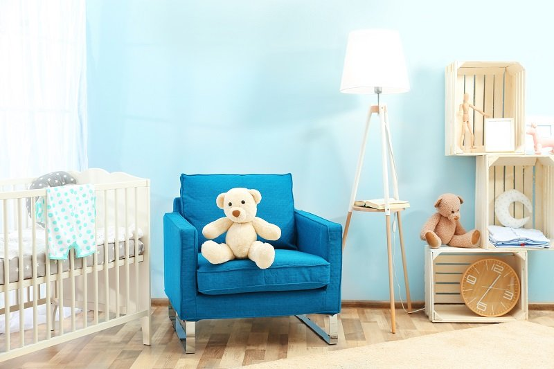 Cute teddy bear on blue armchair in baby room