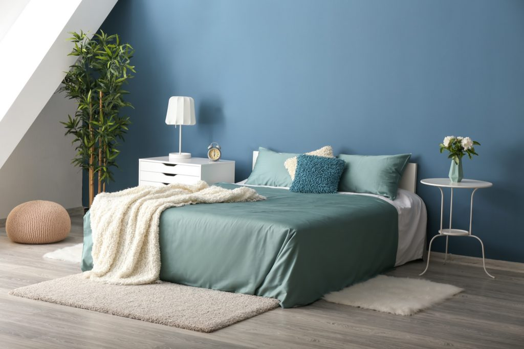 Blue colored bedroom with a comfortable bed that has green linens on it