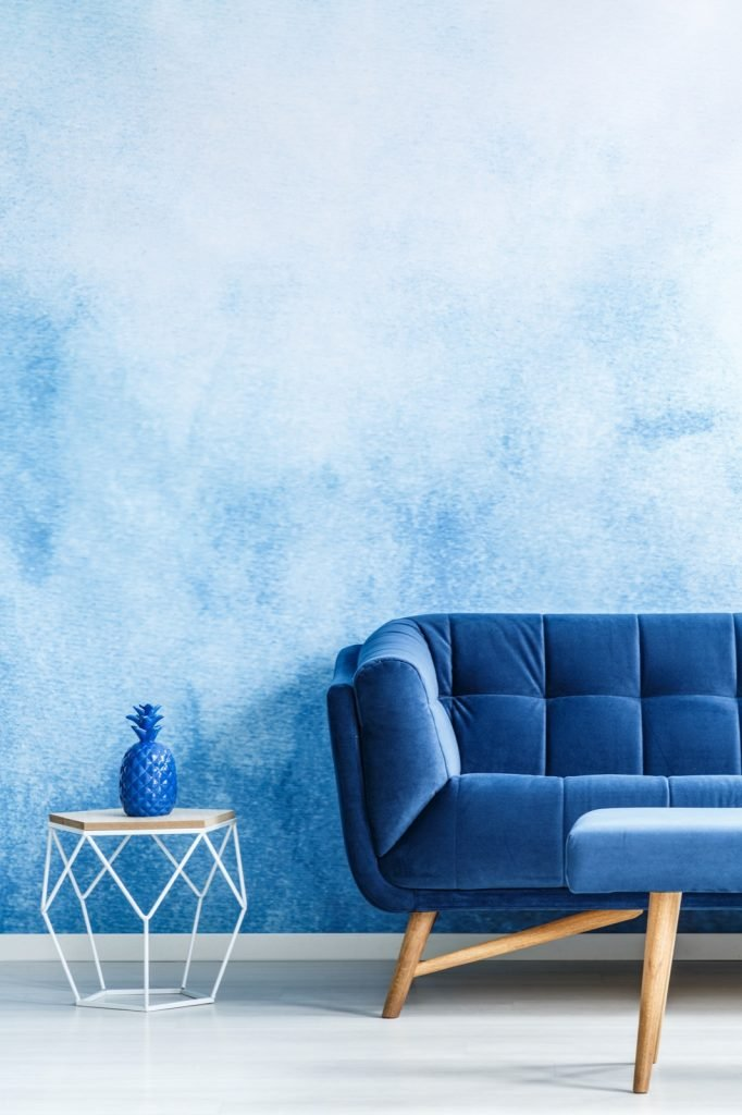 Monochromatic living room interior with blue couch against ombre wall