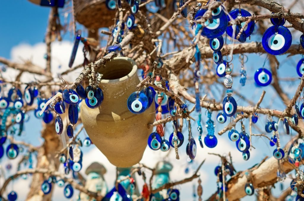 Blue Nazar charms on the branches of a tree used to ward off evil in Cappadocia in Turkey