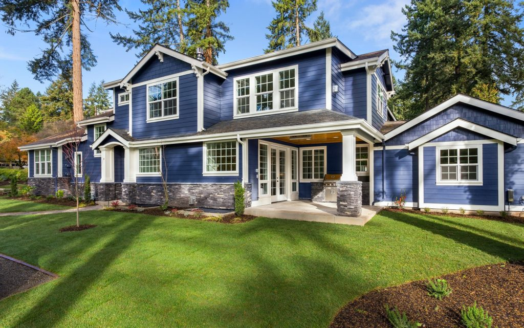 Beautiful blue painted home exterior on sunny day with green grass and backdrop of trees