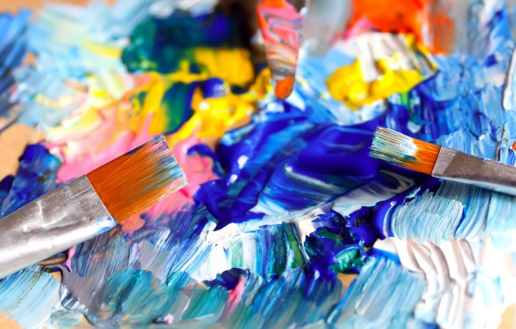 Closeup of paint brushes mixing blue colors on palette
