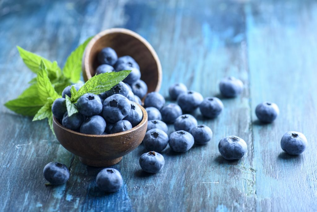 Bowl of colorful fresh blueberries on blue rustic wooden table
