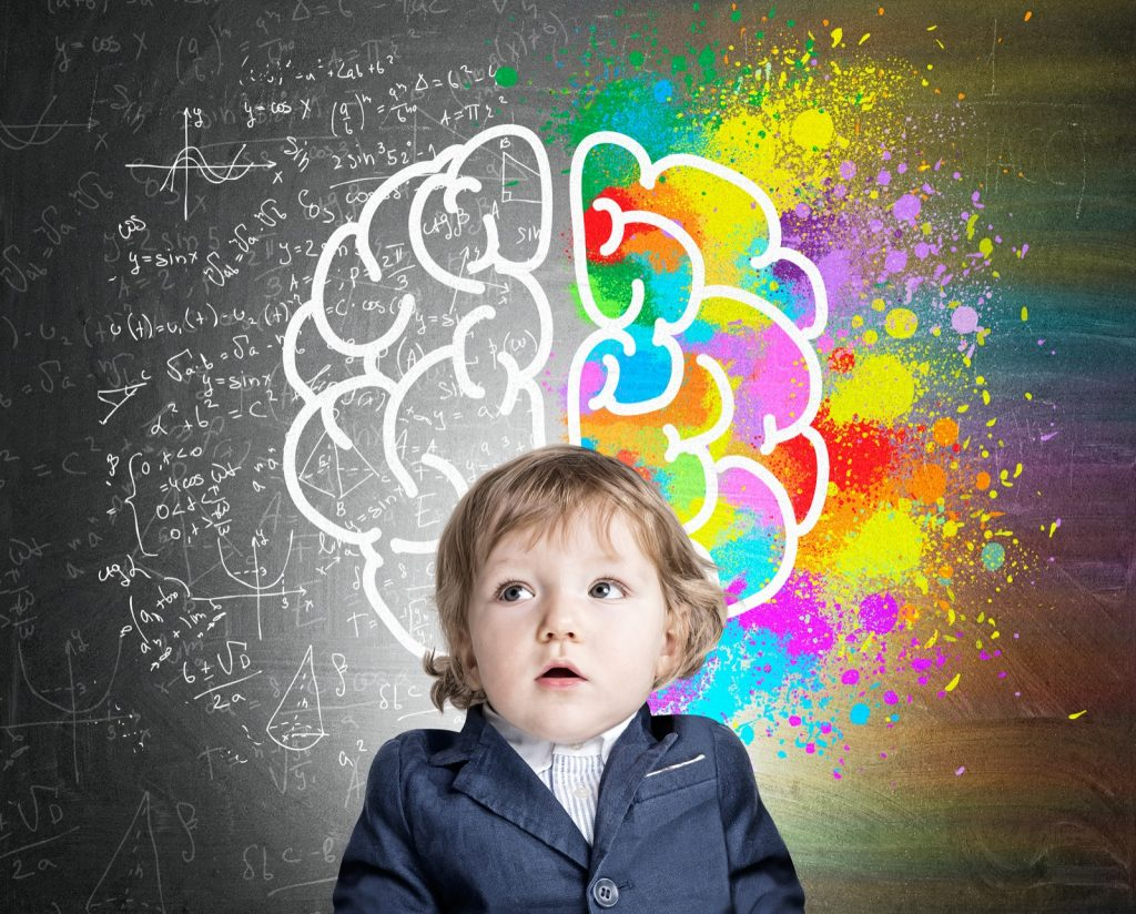 Portrait of boy wearing a suit and standing near a chalkboard with a colorful brain illustrating a kids development