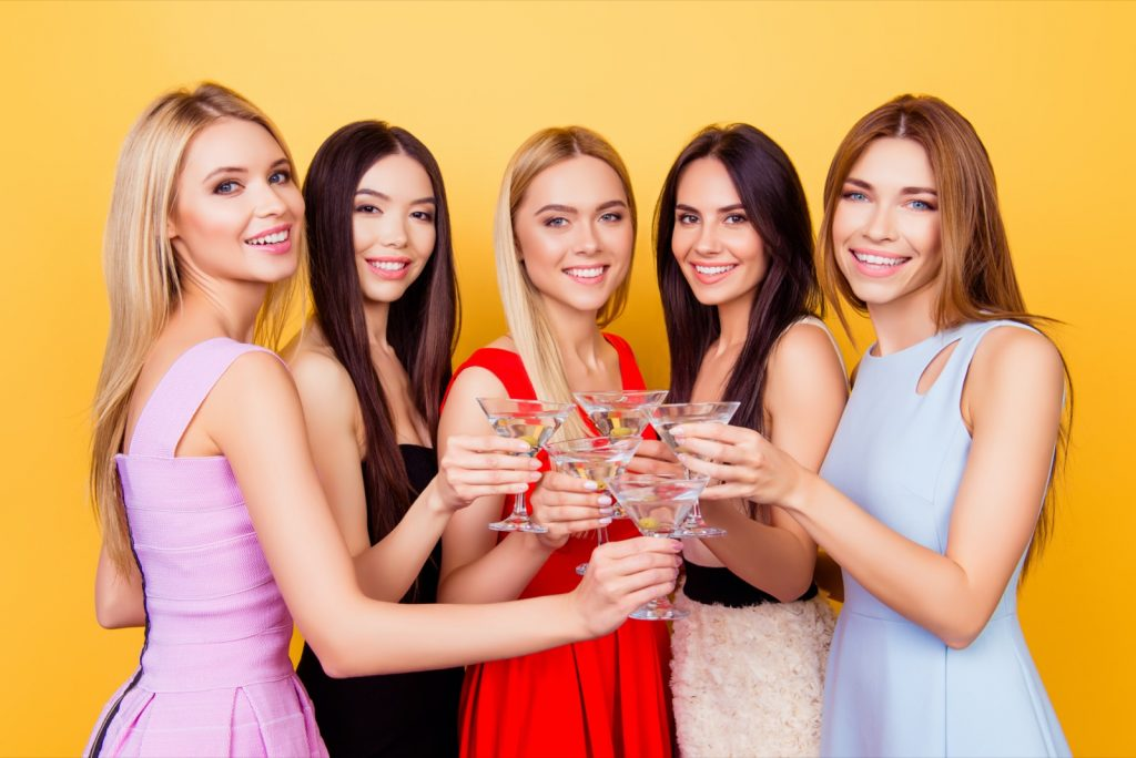 Four bridesmaids and a future bride toasting in colorful cocktail outfits