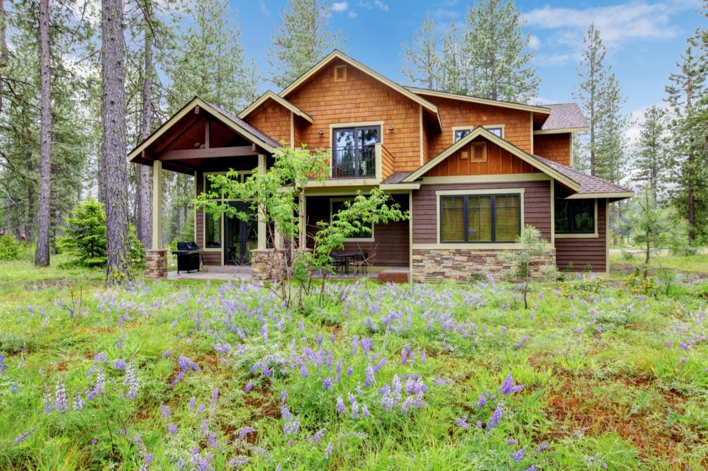 Brown mountain cabin home wood exterior with forest and flowers