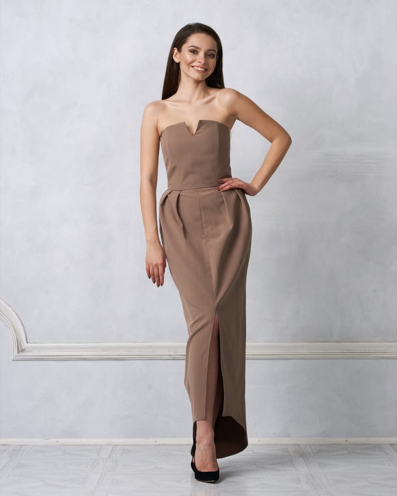 Brunette female model dressed in strapless taupe brown gray formal dress posing in studio