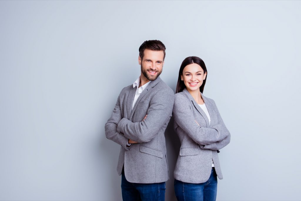 Modern business man and woman in gray suits standing back-to-back with arms crossed