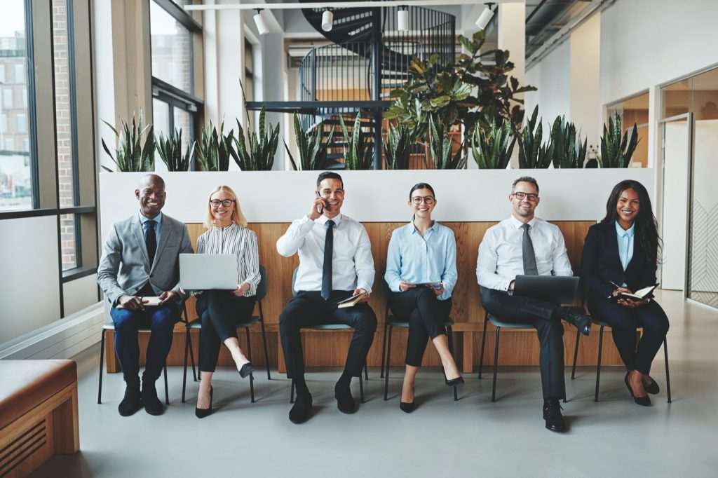 Diverse group of business people in different colored clothes sitting in a row on chairs in an office reception waiting for a job interview