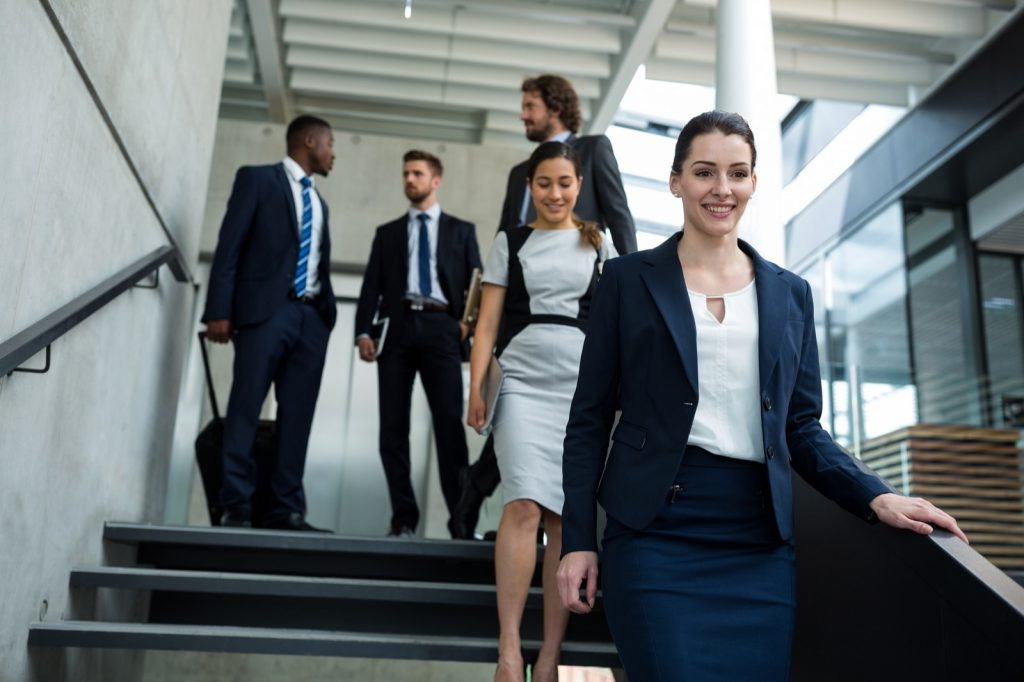 Businesswoman with colleagues walking down stairs in blue clothes