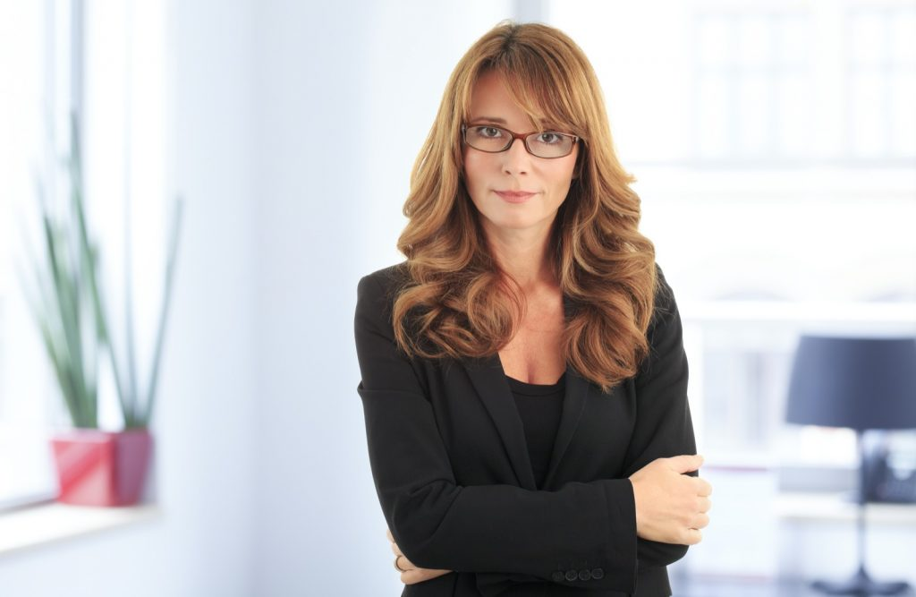 Confident businesswoman standing in office wearing brown glasses