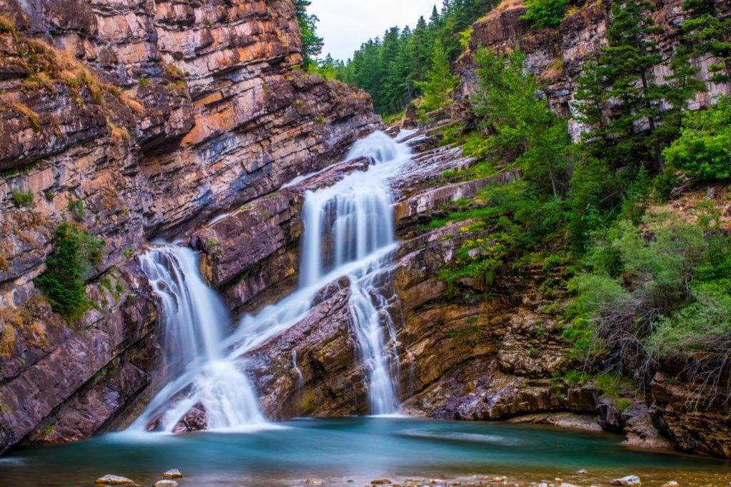 Cameron Falls waterfalls in Alberta, Canada with pink rock walls