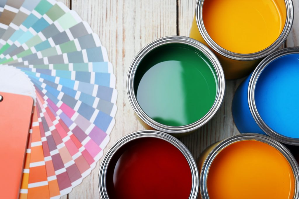 Top view of cans with paint and color palette on wooden background
