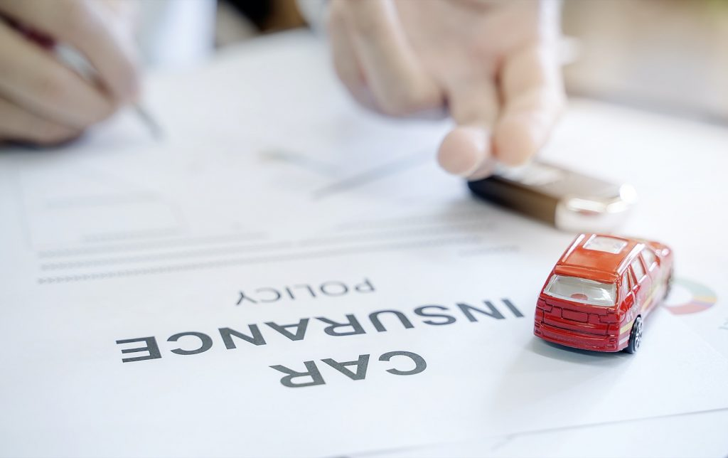 Car insurance policy with red toy car and blur image of male hand