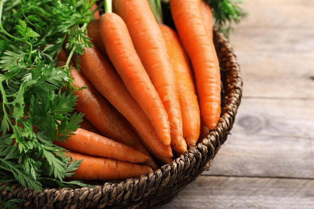 Closeup of a basket with carrots on wooden background