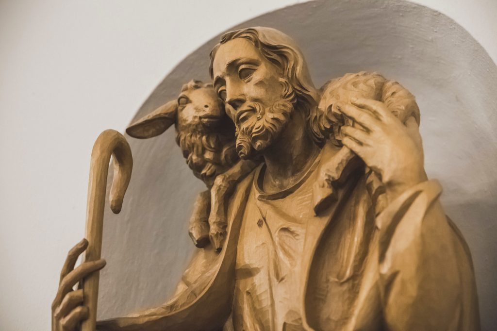 Carved wood statue of Jesus with a lamb on his shoulders in a white church