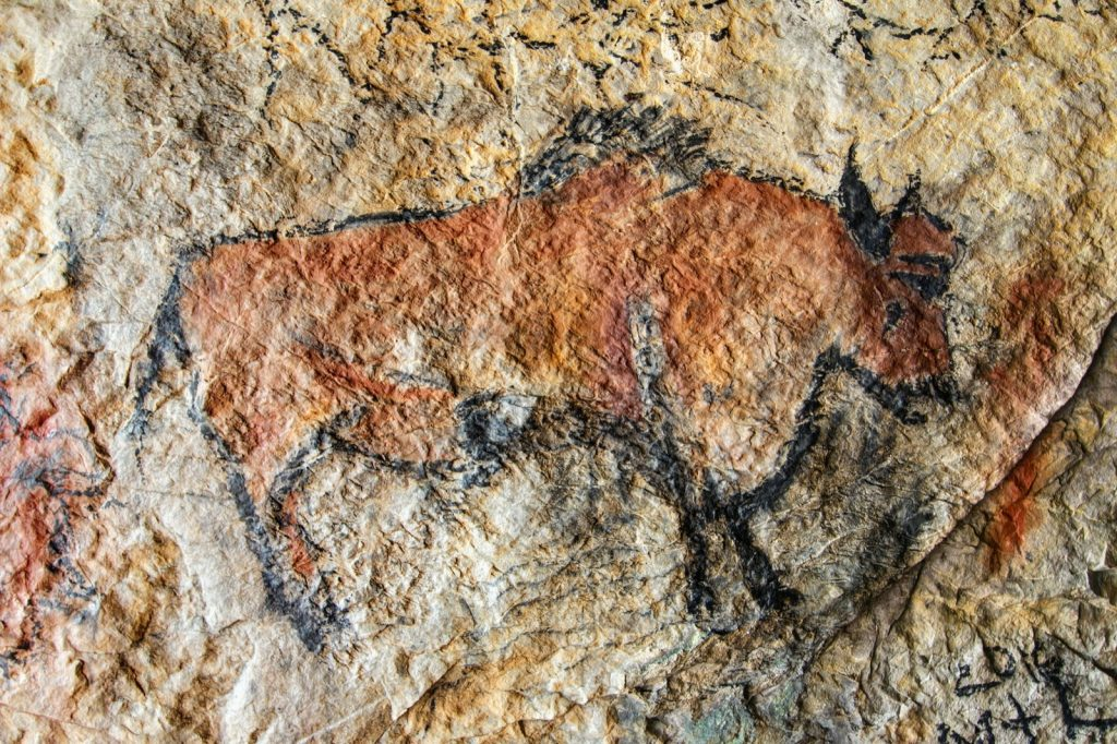 Prehistoric cave painting of orange colored bison on rock wall