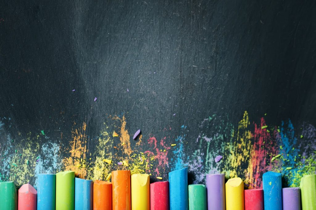Chalk in many different colors on a blackboard background