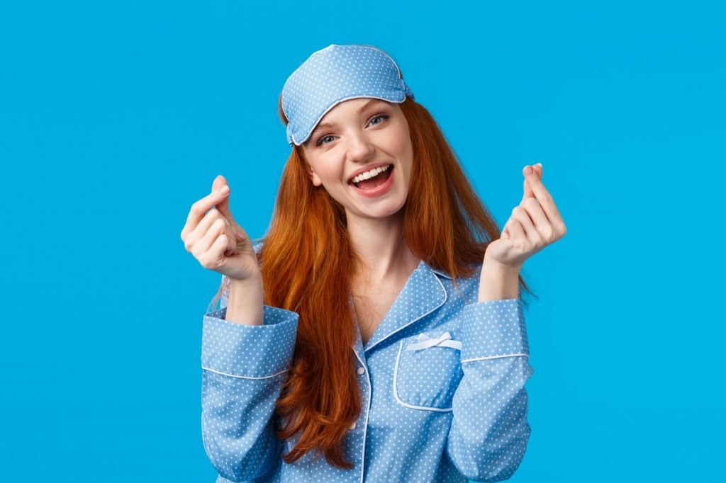 Cheerful redhead girl feeling well rested in nightwear and sleep mask on blue background