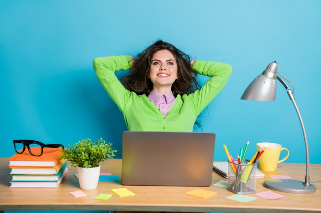 Cheerful woman sitting in home office in front of bright blue colored wall