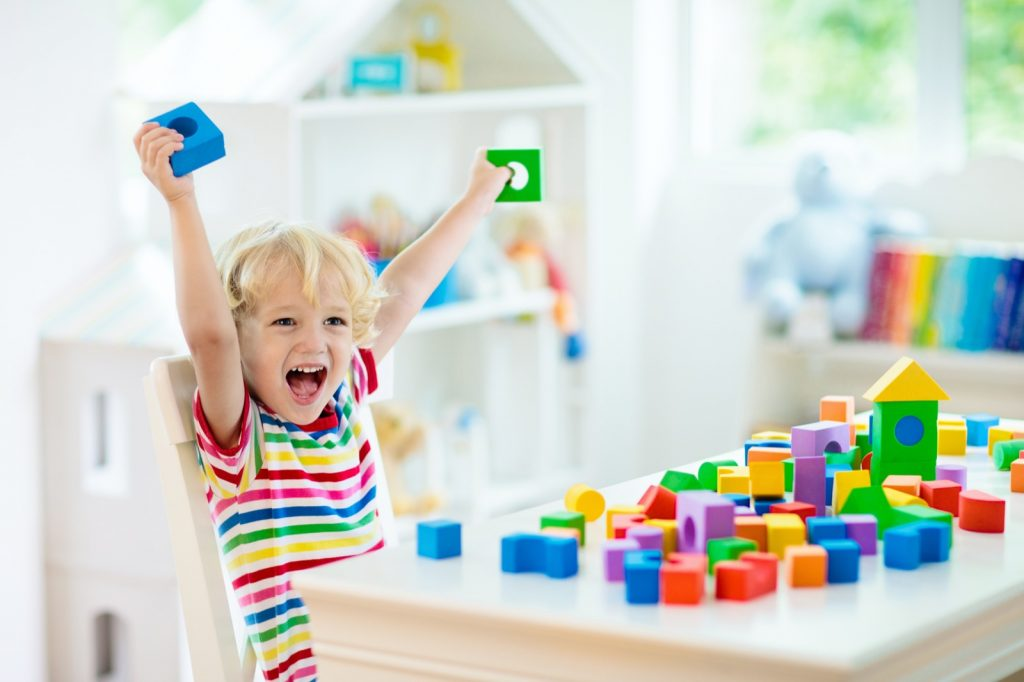 Child building tower with colorful toy blocks and learning about colors
