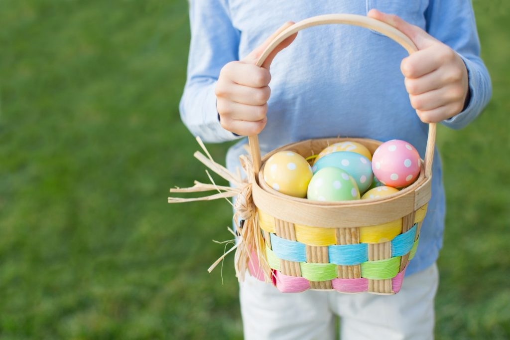 Child holding basket of colored Easter eggs after egg hunt at spring