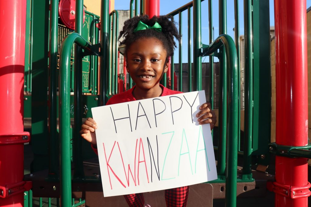 Child holding Happy Kwanzaa sign outdoors with text in black, red, and green colors