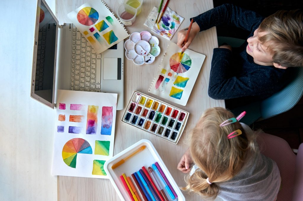 Children painting color wheel and palette with watercolor paints