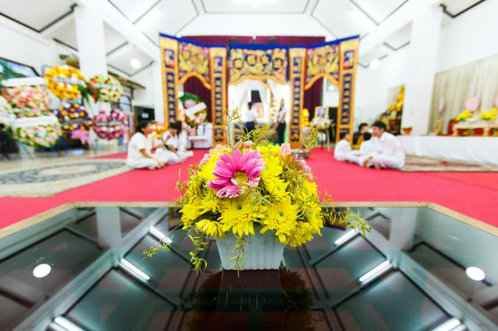 Chinese funeral at temple with people sitting on red carpet in white clothes