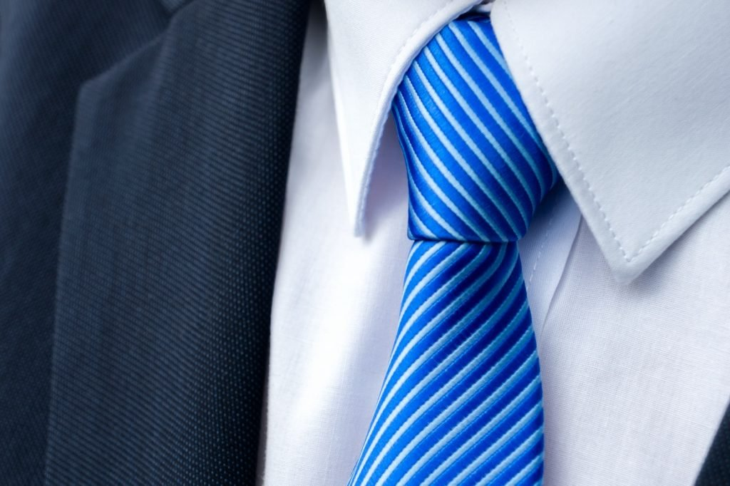 Close-up of a blue colored striped tie on a white shirt and a suit