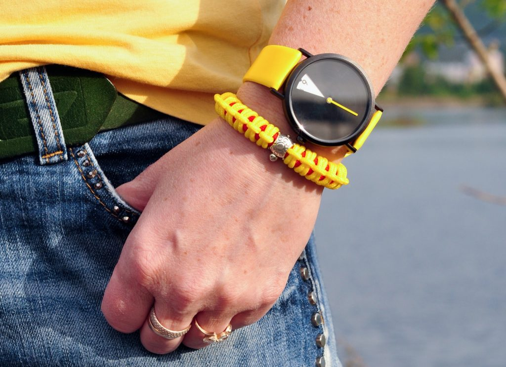Close-up of a bright yellow wrist watch on a summer day