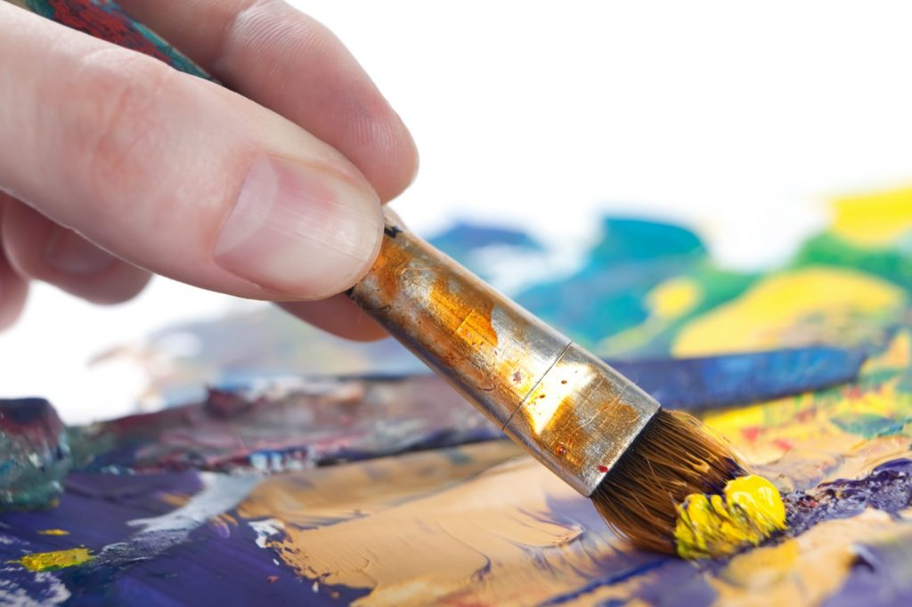 Close-up of hand painting a picture with a paintbrush using yellow colored paint