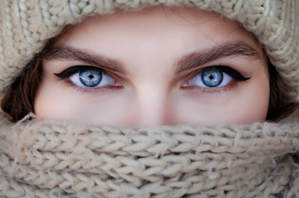 Close-up portrait of a woman in a scarf and hat with clear blue eyes