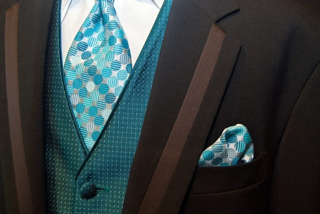 Close-up of teal colored tie on brown suit