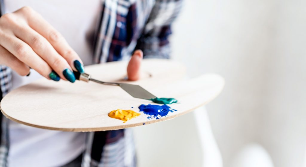 Female hands mixing paints on a wooden art palette