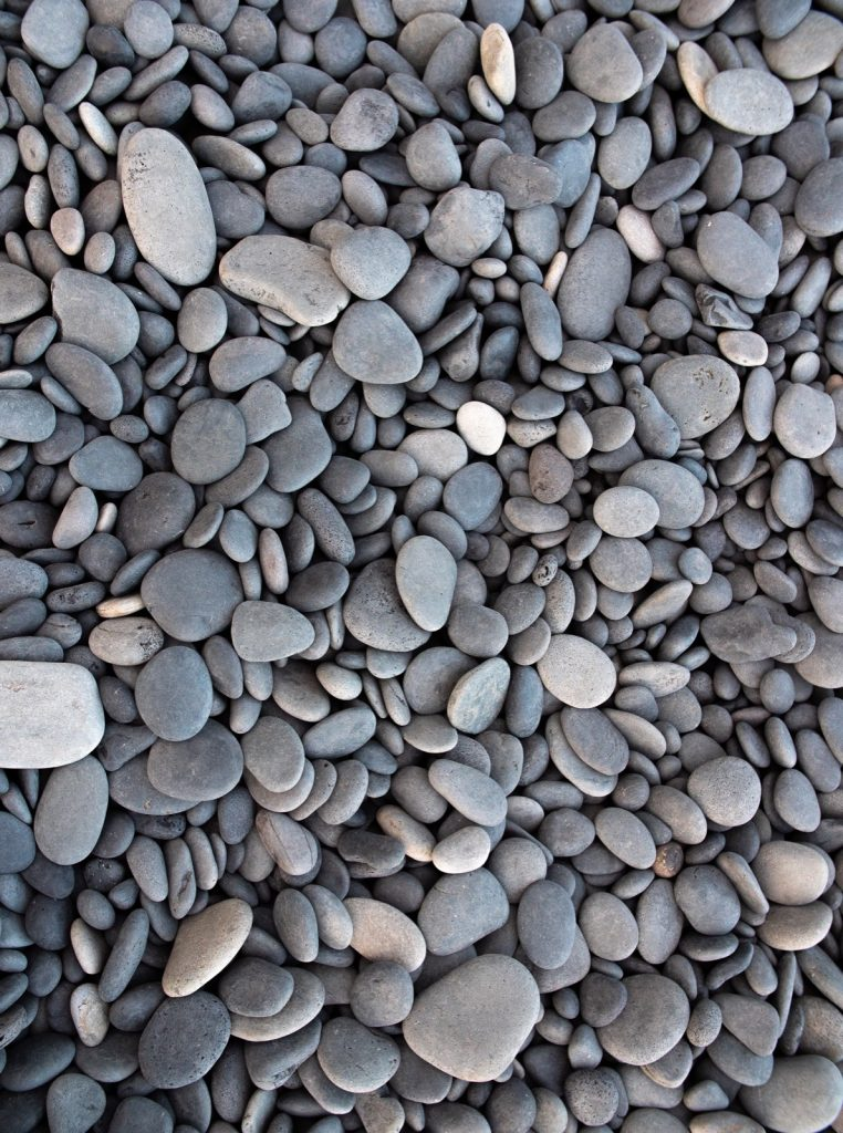 A closeup shot of small grey pebbles on a beach