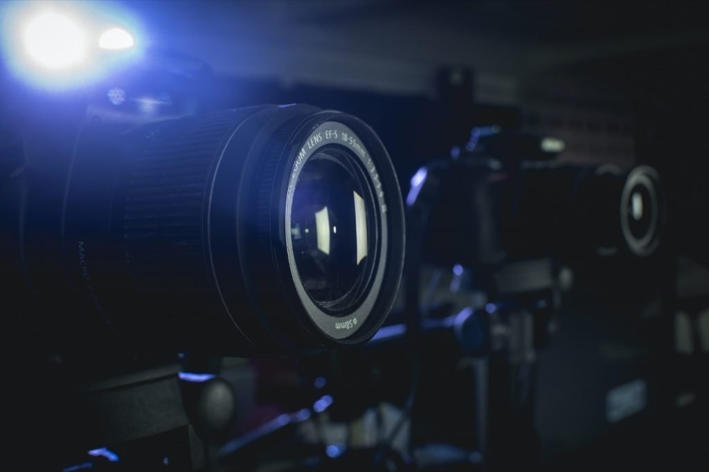 Closeup of a two camera setup and a spotlight in the background