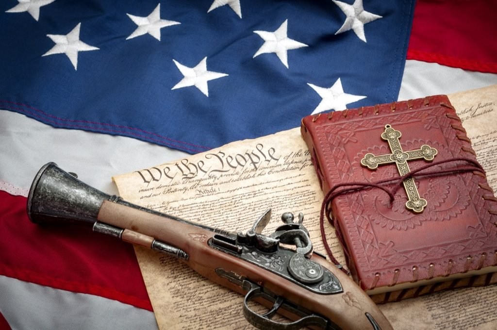 Blue red and white colored American flag with musket and bible