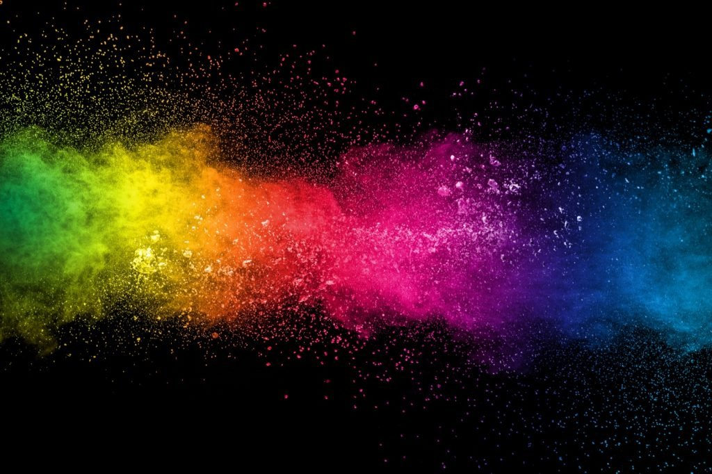 Colorful explosion of paint pigments on a black background