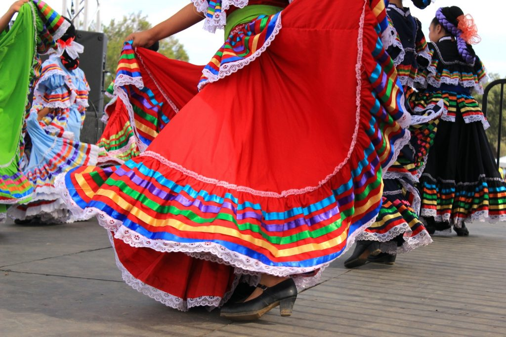 Colorful red and green skirts flying during Mexican dancing at Cinco de Mayo