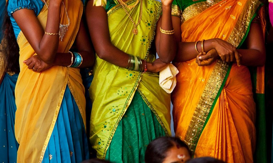 Three Indian women in yellow and orange colored clothing