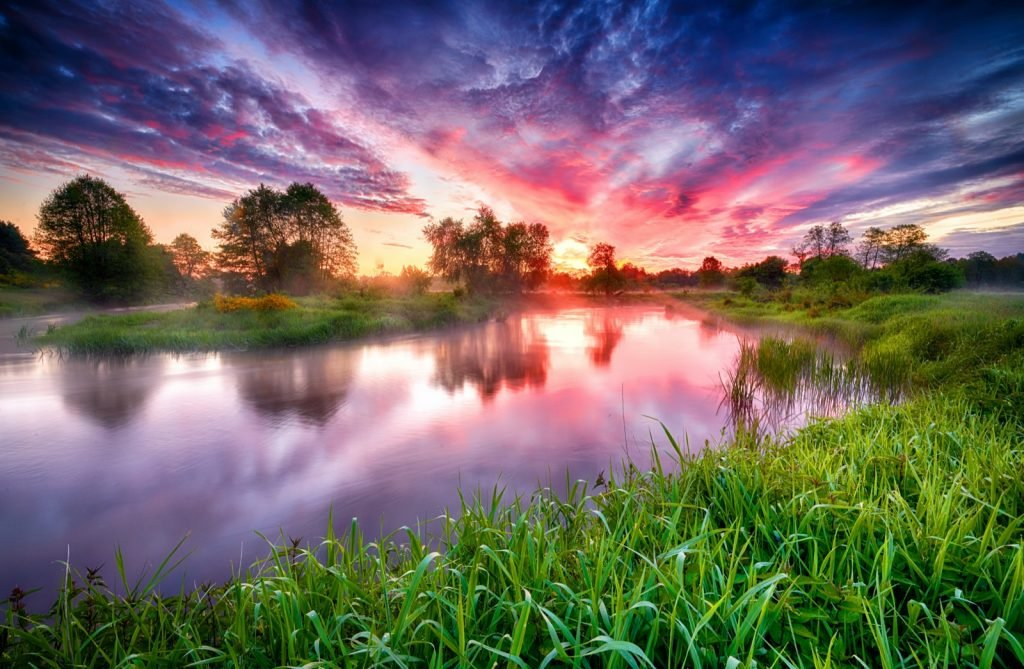 Colorful sunrise over river banks