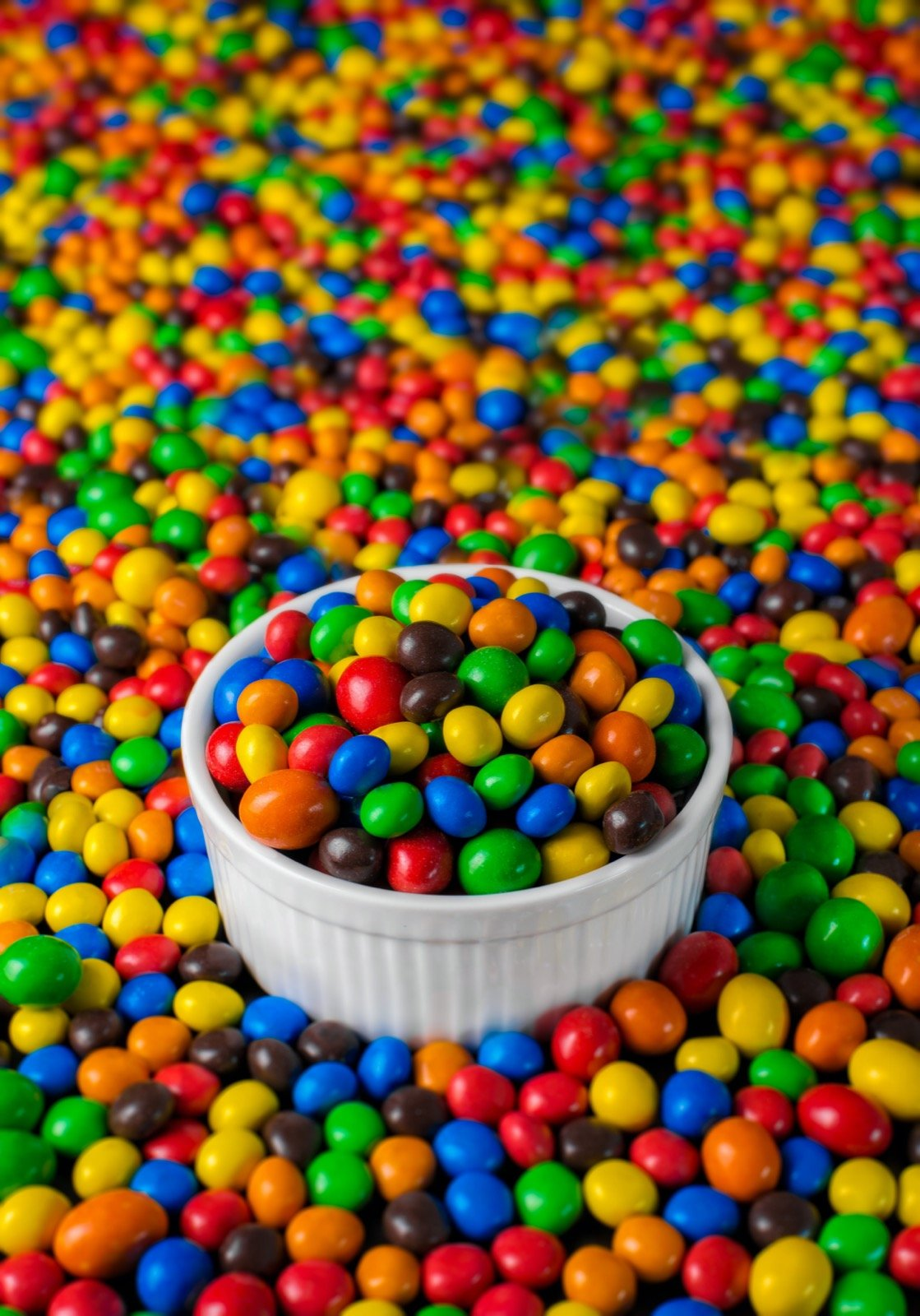 Colorful sweets resembling M&Ms in white ceramic bowl