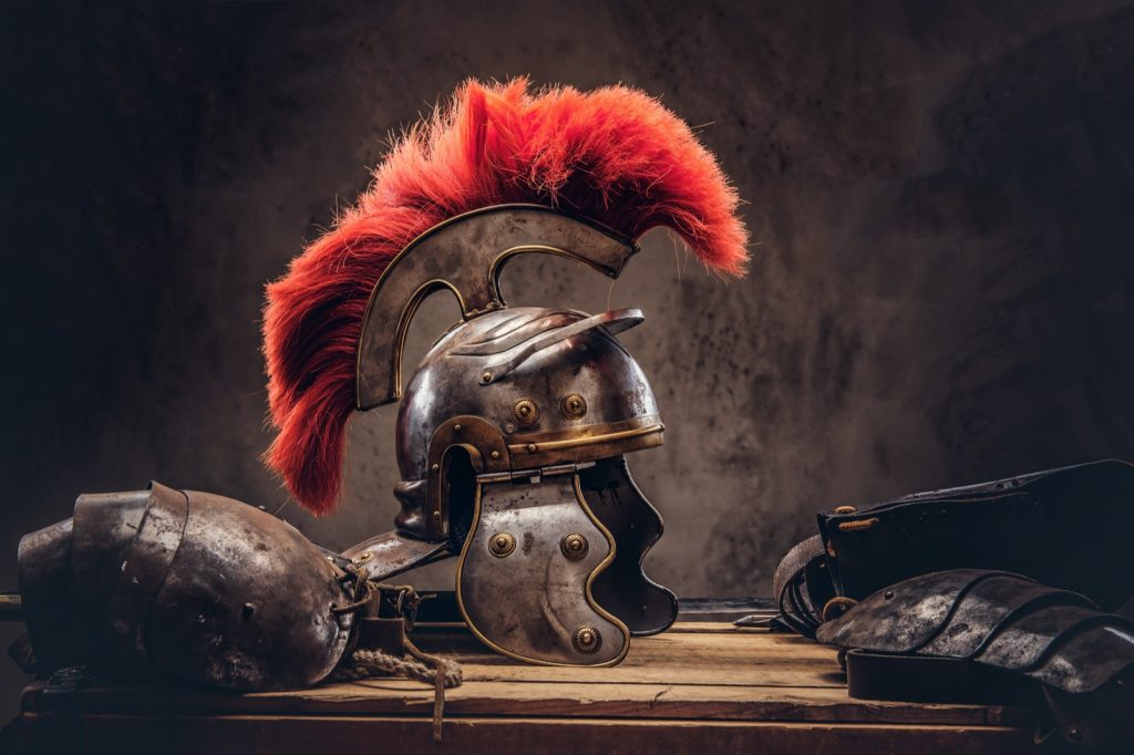 Combat helmet with a red mane from ancient warrior on wooden boards