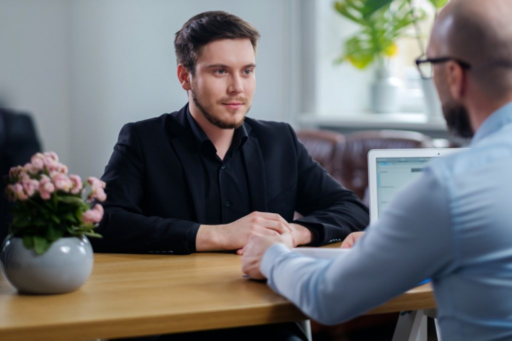 Confident young man attending job interview in black clothes