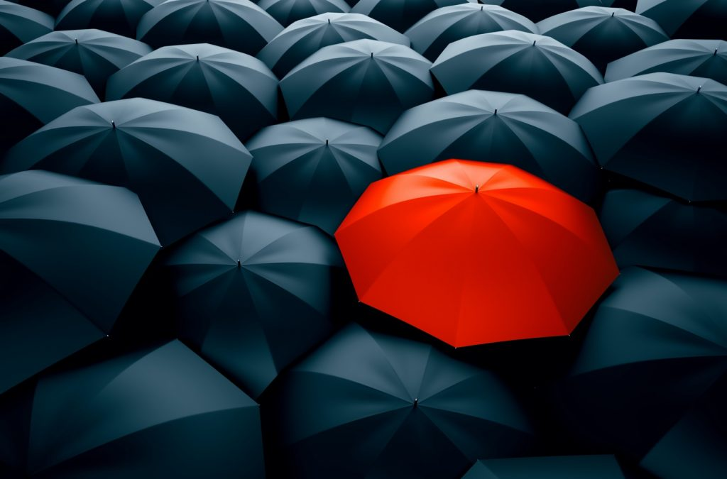 Contrasting red umbrella stands out in a crowd of black umbrellas